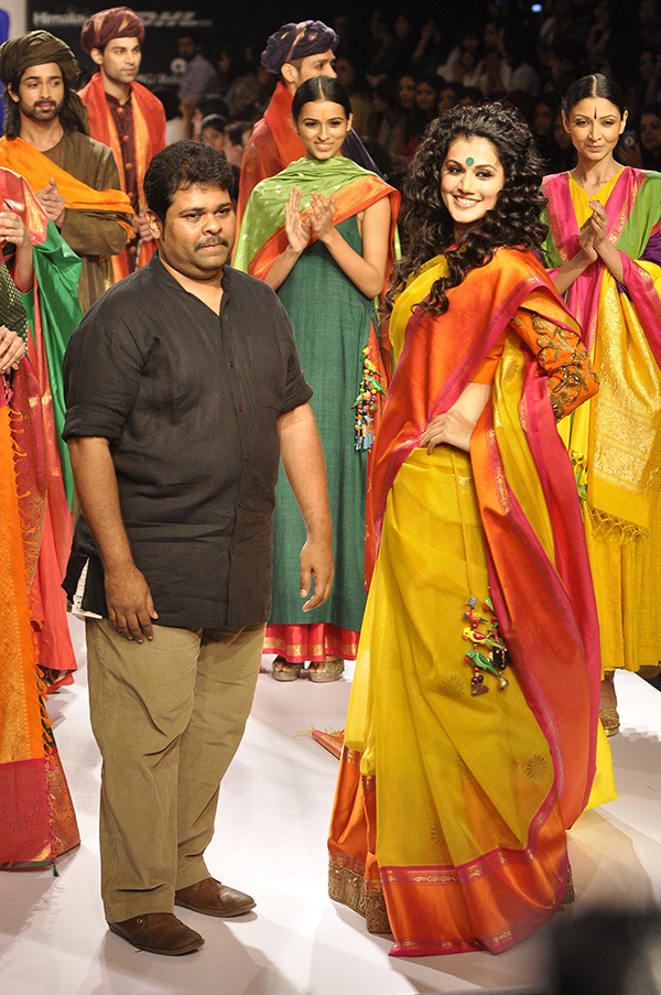 Fashion designer Gaurang Shah walks the ramp with actor Taapsee Pannu during the Lakme Fashion Week (LFW) Winter/ Festive 2014, in Mumbai, on Aug. 22, 2014. (Photo: IANS)